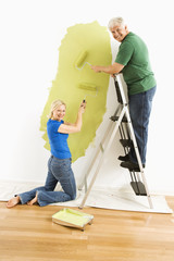 Couple painting wall.