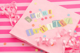 cut out letters spelling you're invited on pink napkins