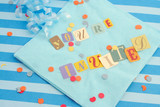 cut out letters spelling you're invited on baby blue napkins