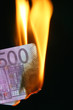 500 euro bill on fire over black background