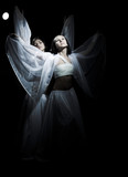 Two girls in white raiment dancing in semidarkness