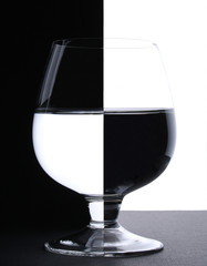 a glass with water in backlight on the black and white contrast