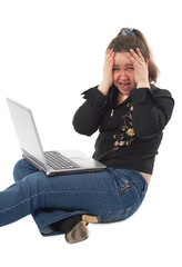 Sad girl with laptop sits on floor isolated