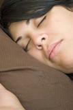 A young brunette woman is fast asleep in her bed. poster