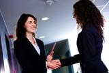 Happy businesswomen shaking hands at office corridor poster