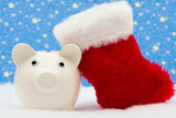 Piggy bank and red stocking sitting on snow and star background