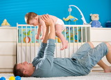 Father lying on back and lifting baby boy ( 1 year old ) at home