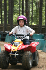 Young boy out for a ride on a mini quad