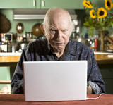 Grumpy Senior in Dining Room with a Laptop Computer