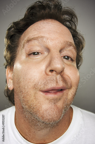 Goofy Guy with Obnoxious Expression on a Grey Background.