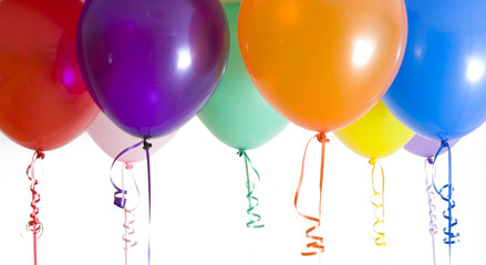Close up of variety of balloons with ribbons brightly lit