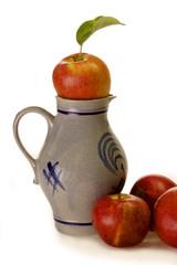 Apfelweinkrug mit frischen Äpfeln auf hellem Hintergrund