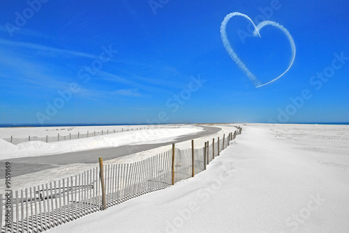 Sky writing heart over white sand on coastal island