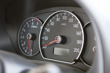 A closeup of a car dashboard with a speedometer