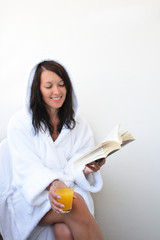 Young smiling woman with orange juice reads book