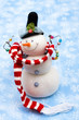 Snowman wearing scarf on blue snowflake background