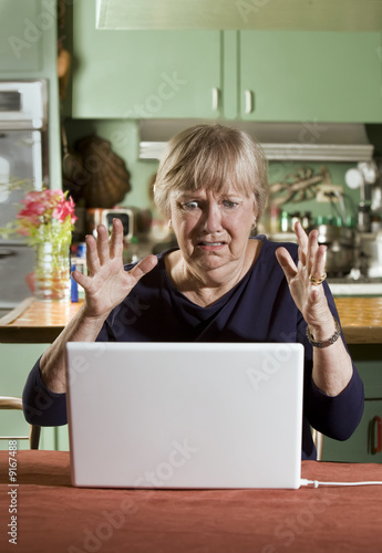 Shocked Senior Woman in Dining Room with a Laptop Computer
