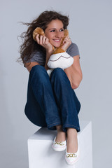 Brunette is sitting on white box with a puppy