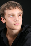 Teenage male in casual attire looking into the distance poster