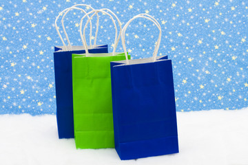 Three colourful gift bags on snow with star background