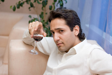 Portrait of the young attractive man with glass of red wine
