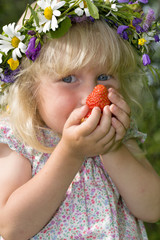 happy little girl in flowers wreath with strawberries in hands