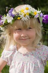 happy little girl in flowers wreath on green meadow