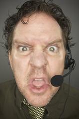 Irate Businessman Wears Phone Headset - Grey Background.