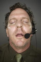 Businessman Sleeps Wearing a Phone Headset -  Grey Background.