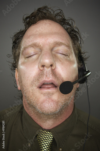 Businessman Sleeps Wearing a Phone Headset -  Grey Background.