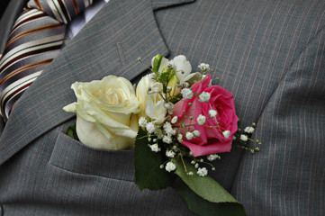 White and pink roses boutonniere on groom's wedding suit