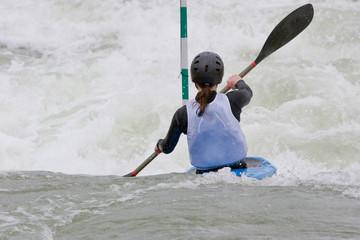 A canoeist paddling through fast running white water