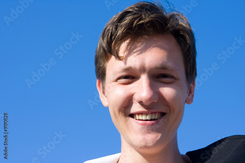 Smiling young man on blue sky background
