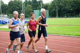 Group of running people on a race track