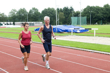 Senior couple running together on a track in a stadium.