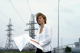 Woman engineer with safety hat drawings and electrical towers poster