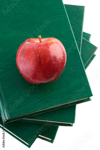 A red apple red on a green book on a white background