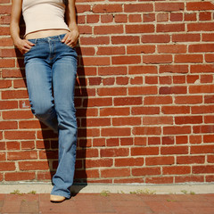 Fashionable closeups of womans mid section against brick wall.