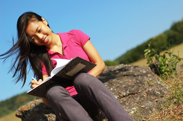 Girl writing in notebook in a field.
