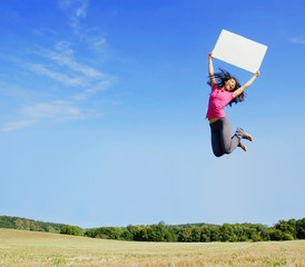 Girl jumping with a blank sign in a field.