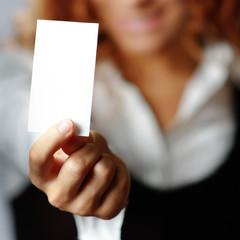 Pretty girl holding white blank media, against white.
