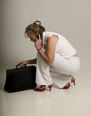 Business woman kneels to her briefcase while on the phone.