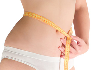 Woman measuring waist with a tape measure. Isolated