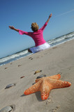Starfish and tranquil woman on the beach poster