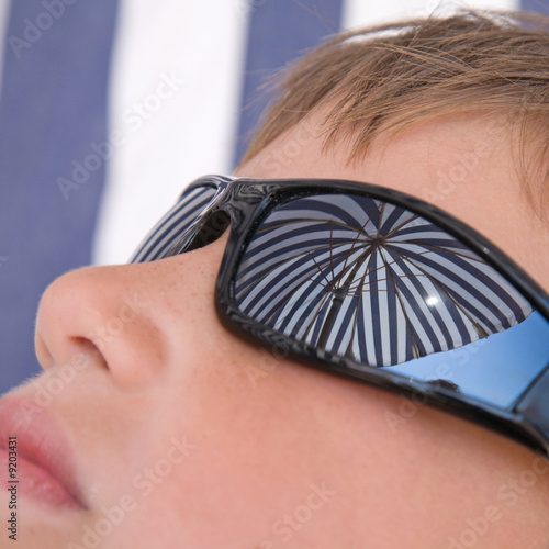 reflection of beach hut dome in boy's sunglasses