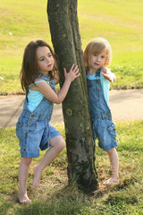 Two sisters touching a tree