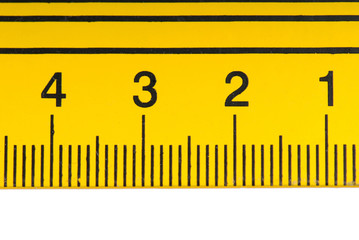 Macro shot of numbers on a yellow steel ruler.