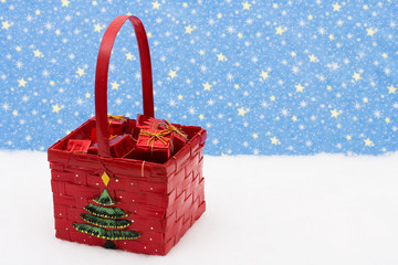 Red basket filled with presents with tree on it sitting on snow
