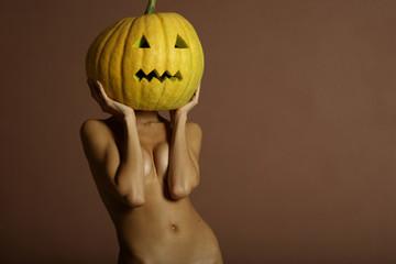 Sexy lady with big pumpkin on head. Surrealstic portrait.