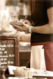 Toned outdoor cafe scene with waitress taking order - 9211098